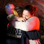 A photo of people comforting each other after a mass shooting at a bar in Thousand Oaks, California.