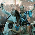 Two women wave their phones in the air at a crowded music festival.