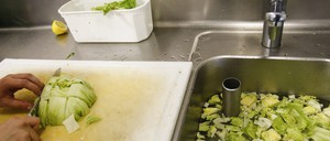 A cook chops vegetables and dumps the scraps in a sink filled with water