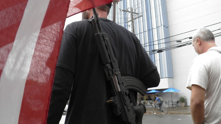 A man with a gun strapped to his back walks down the street near the University of Texas, as he and other pro-gun advocates prepare for a 'mock mass shooting' in 2015. The demonstration was intended to show the need for firearms on campus.