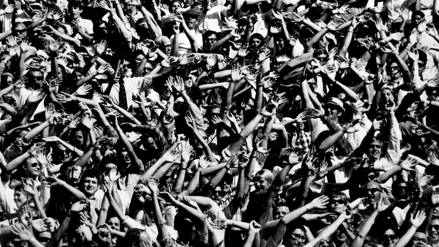 Football fans cheering as the University of Kansas Jayhawks score two touchdowns during a game against Syracuse, winning the game