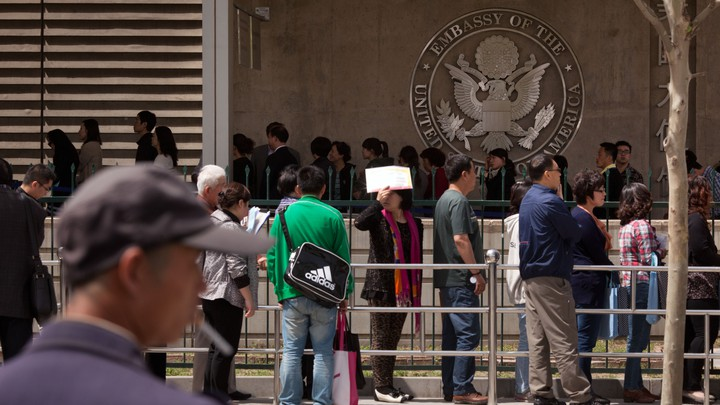 People wait in line outside the visa section of the U.S. embassy in Beijing in 2012.