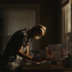 A medic leans over a desk in a darkened room, preparing medical supplies.