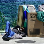 A man sleeping on a sidewalk in Los Angeles.
