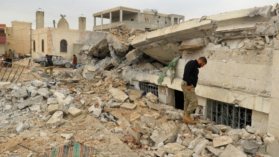 People inspect a damaged mosque after an airstrike was conducted on the rebel-held village of al-Jinah in Aleppo, Syria, on March 17, 2017.
