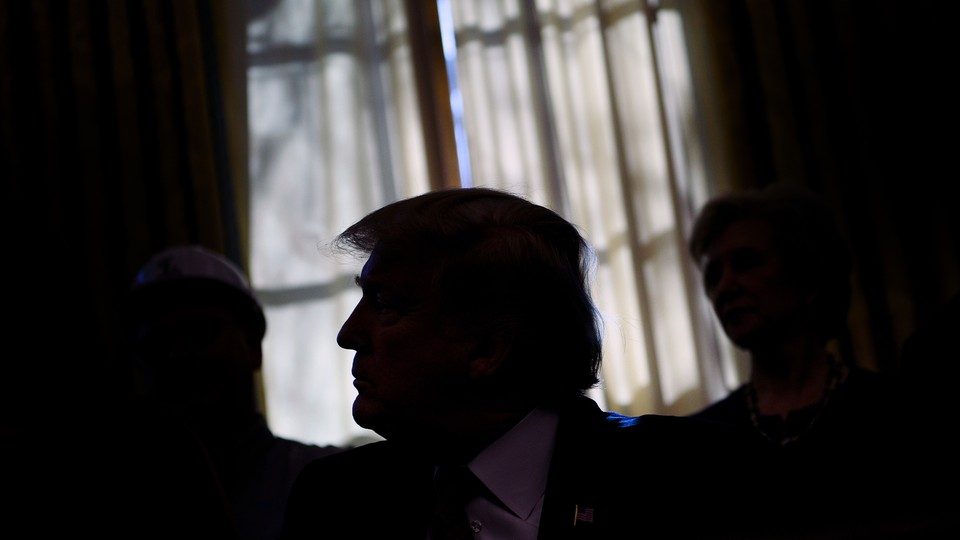 Trump sits in front of a window with his face obscured by shadows.
