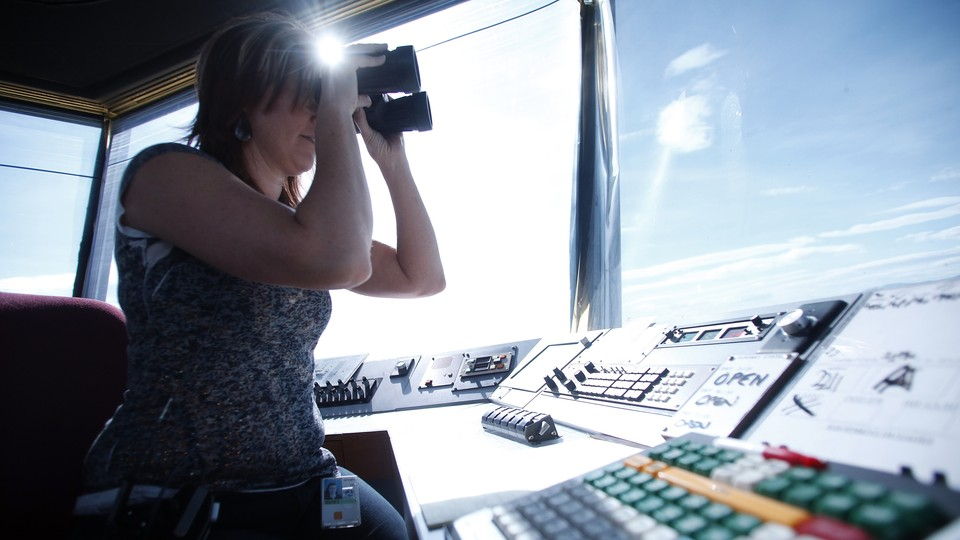 An Air Traffic Control specialist watches plane traffic from the control tower at the Ogden-Hinckley Airport in Ogden, Utah