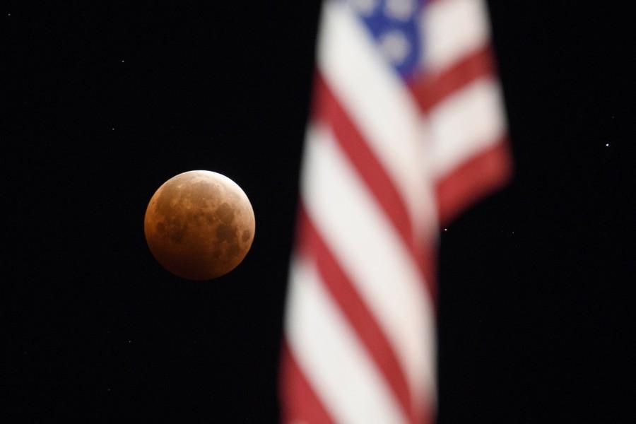 A full moon is seen beyond an American flag.