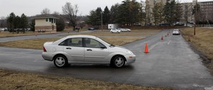 A driver's ed car goes through a course in a parking lot.