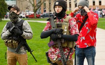 A photograph shows three men standing together—two carry firearms, and two are wearing floral shirts.