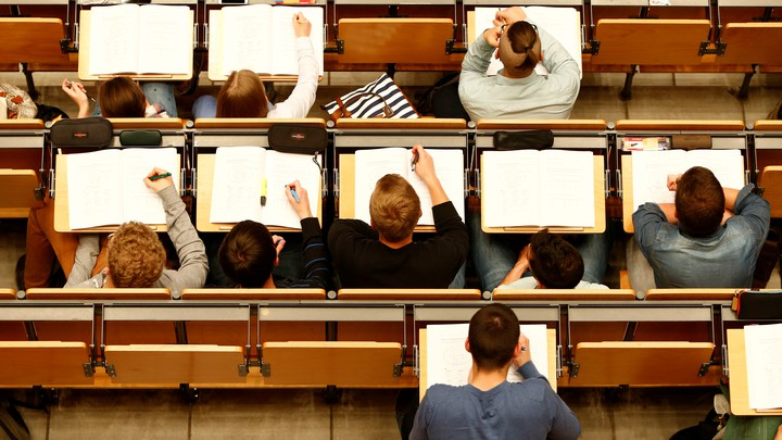 An overhead shot of students with open notebooks on desks in a lecture hall