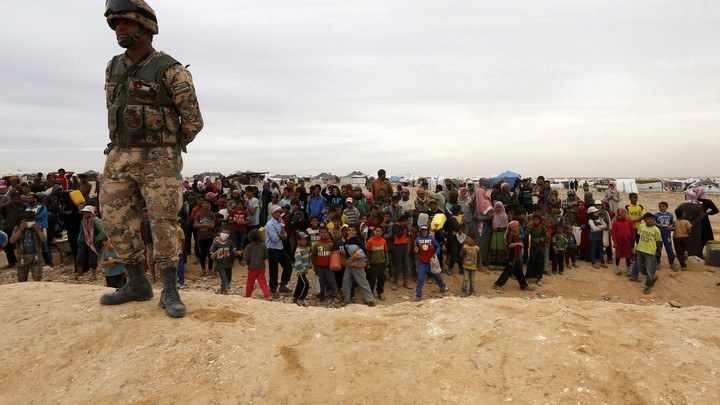 A Jordanian soldier stands guard as Syrian refugees, stuck between the Jordanian and Syrian borders, watch a group of them cross into Jordanian territory.