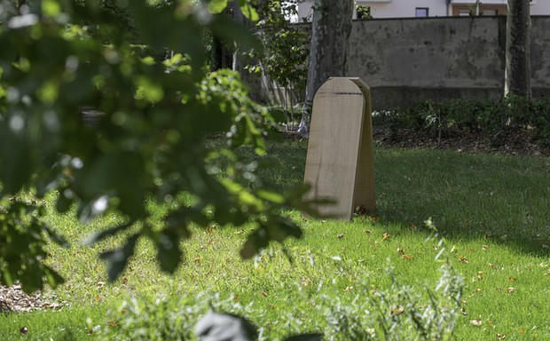 A wooden tombstone marks a grave in a green burial area in Paris.