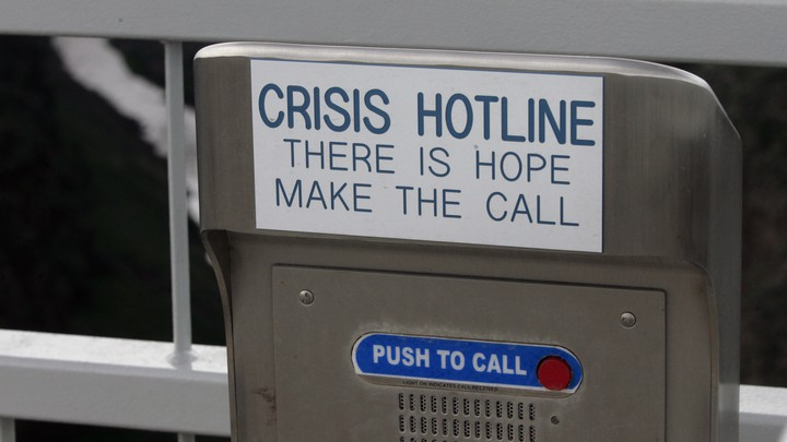 """A metal box with a red button that says """"push to call,"""" and a placard reading """"Crisis Hotline. There is hope make the call"""""""