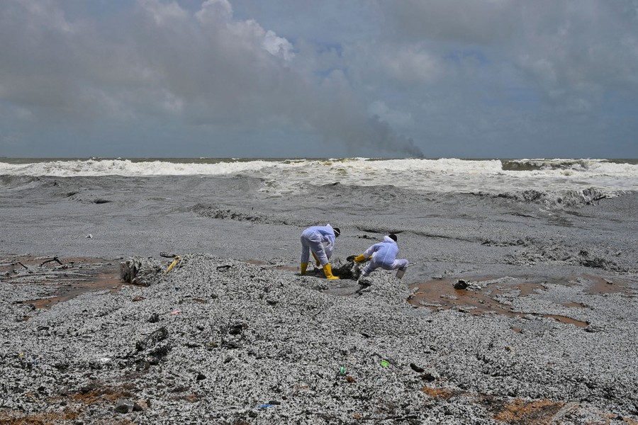 Navy members work to remove debris from a beach.