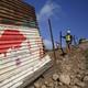 A crew removes part of a border wall near Tijuana, Mexico.
