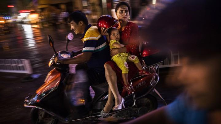 A Uighur family rides a scooter through Kashgar, Xinjiang, China, in 2017