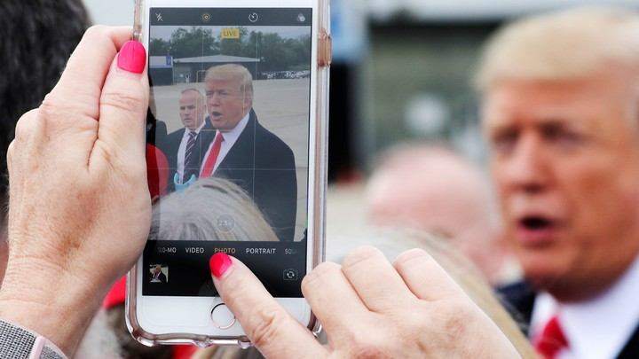 Someone takes a photograph of President Trump on a phone, with Trump visible in the background.