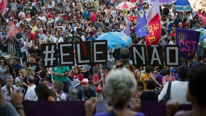 """Demonstrators protest in Rio de Janeiro days before Bolsonaro was elected. They told a large sign saying """"#EleNao,"""" or """"#NotHim."""""""
