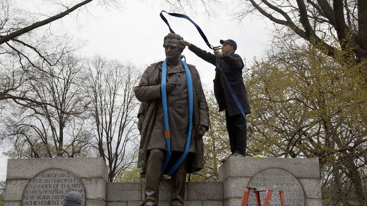 A worker tosses a strap over a statue