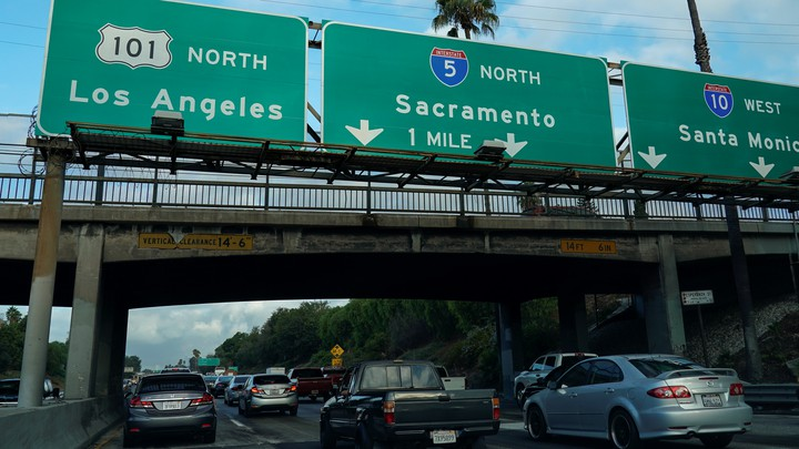 Morning traffic makes its way along a freeway interchange in Los Angeles. The traffic signs read Los Angeles, Sacramento, and Santa Monica.