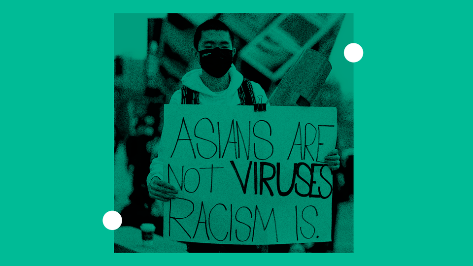 """Protester with a sign that reads """"Asians are not viruses - racism is"""""""