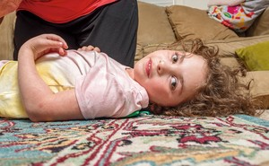 Girl with curly hair lying on colorful carpet with head turned toward the camera, with someone kneeling next to her and couch in background