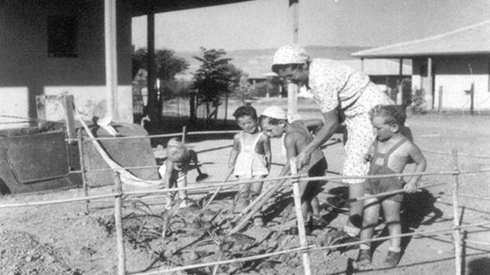 A woman and children tending a garden