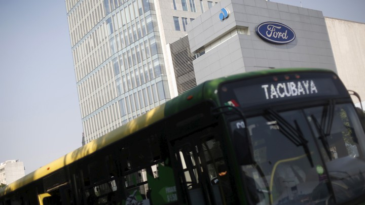 A bus passes in front of a Ford logo near a sales store of the automaker in Mexico City.