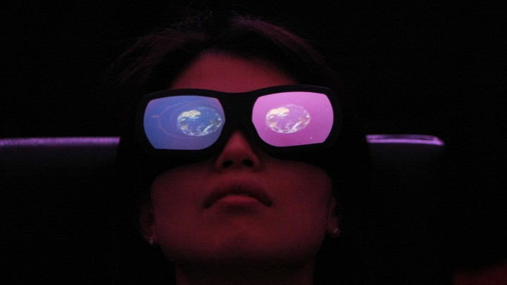 A person wears large glasses with one red and one blue lens and an image of the Earth reflected in each.