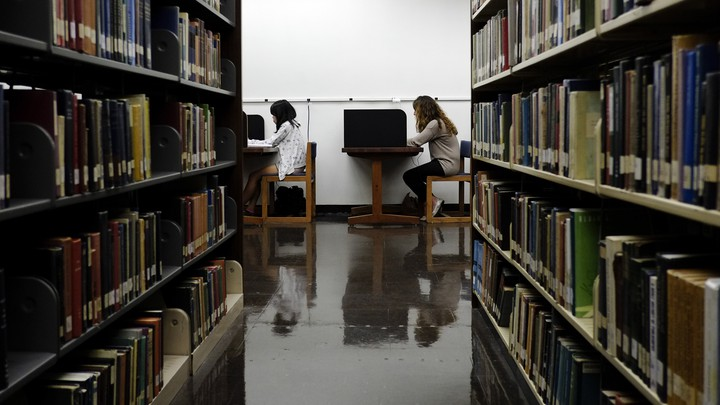 Students sit in a library.