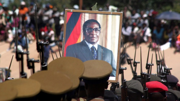 A portrait of Robert Mugabe is held up by Zimbabwean soldiers.