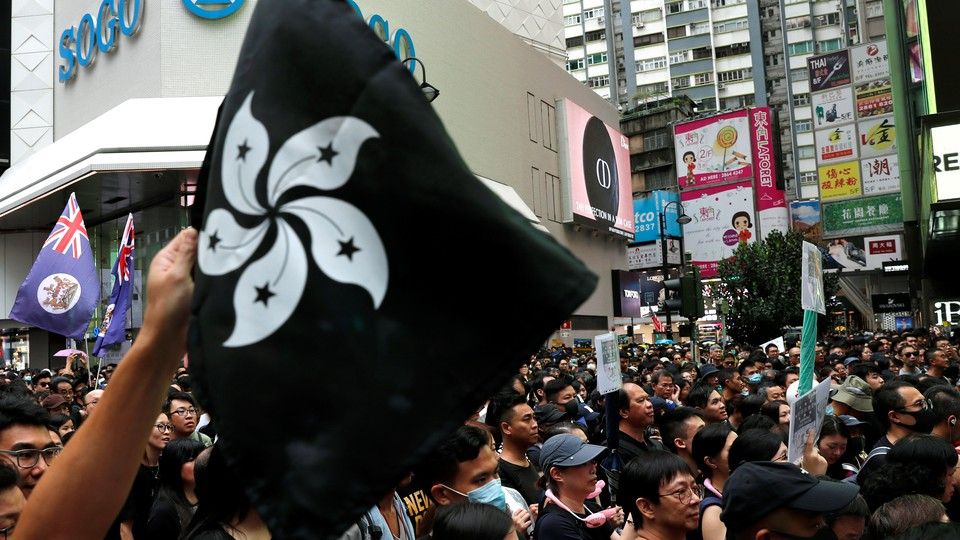 A protester holds up a black version of Hong Kong's flower-emblazoned flag during a packed pro-democracy rally.