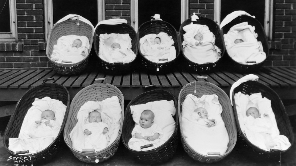 Ten babies, all but one sleeping, rest in baskets on a porch outside a maternity ward.