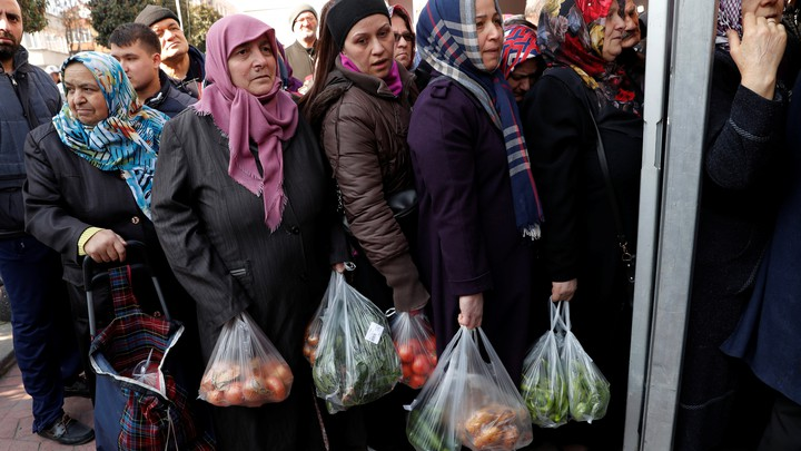 People wait in line to buy vegetables at a tent set up in Istanbul by the municipality.