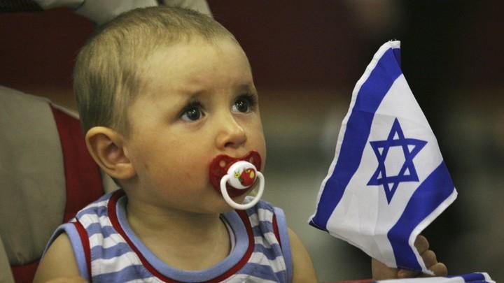A baby holds an Israeli flag.