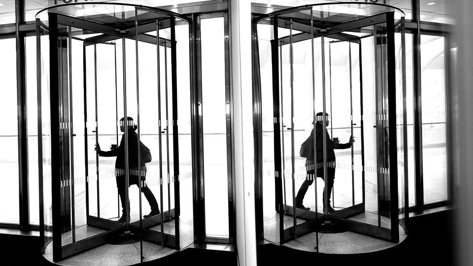 A woman walks through an office's revolving door next to a mirrored wall.
