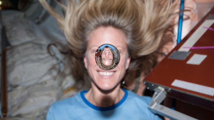 NASA astronaut Karen Nyberg smiles behind a floating bubble of water on the International Space Station