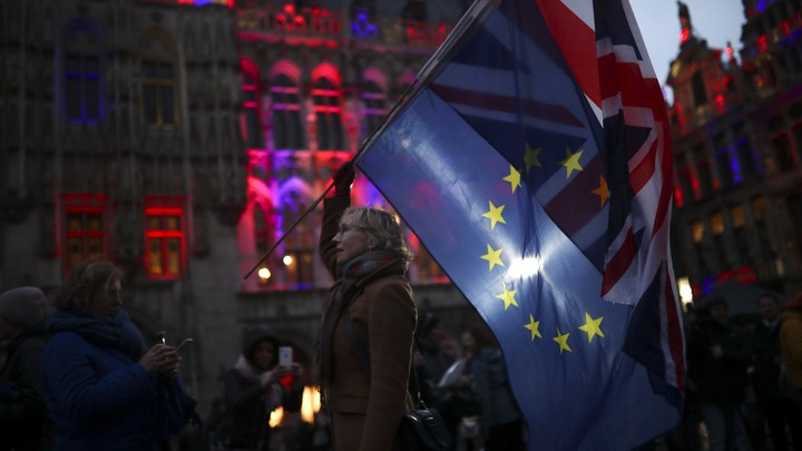 A woman holding the European Union and Union Jack flags.