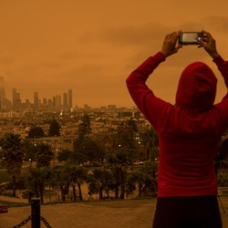 A woman taking a photo of an orange sky