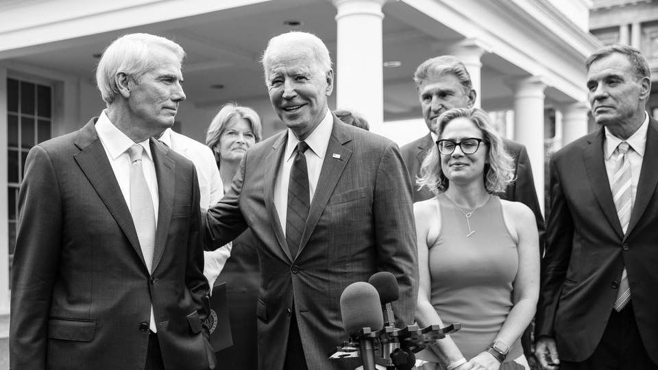 Biden surrounded by senators, while addressing the media