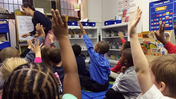Kids, both black and white, raise their hand at Detroit Prep, an intentionally diverse school.
