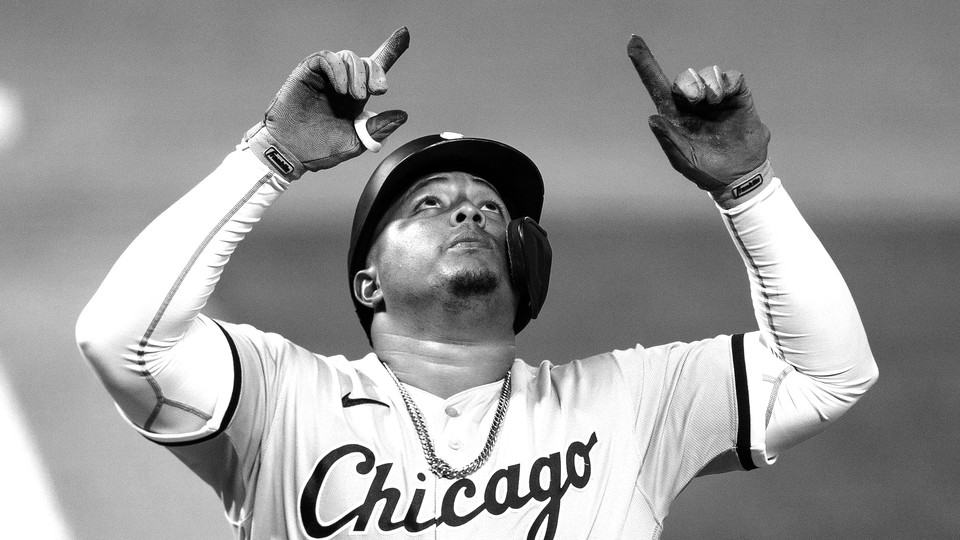 A baseball player looks up and points his index fingers to the sky.