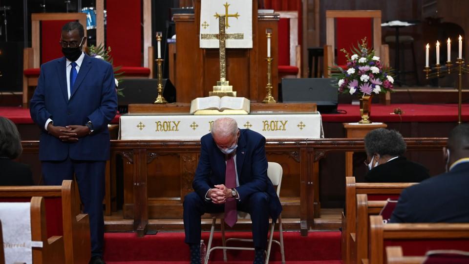 Joe Biden sits in a church with his head bowed.