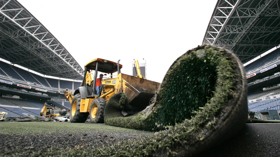 A truck removes artificial turf from a football stadium.