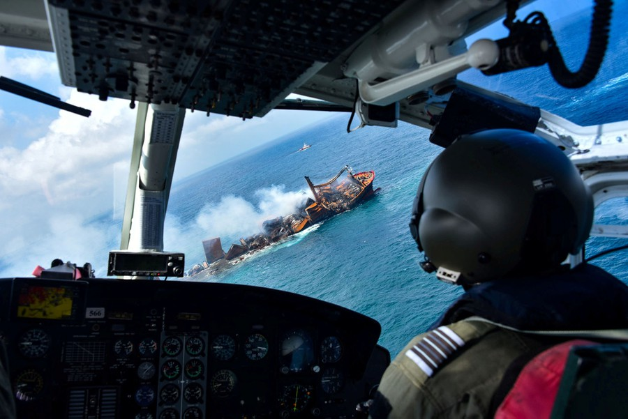 A view from an aircraft interior, showing a burning cargo ship seen through the front windows.