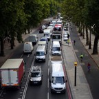 Cars sit in a traffic jam while cyclists ride by in Central London.