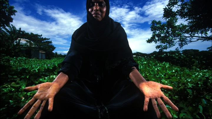 A woman displays her hands in front of a planted field.