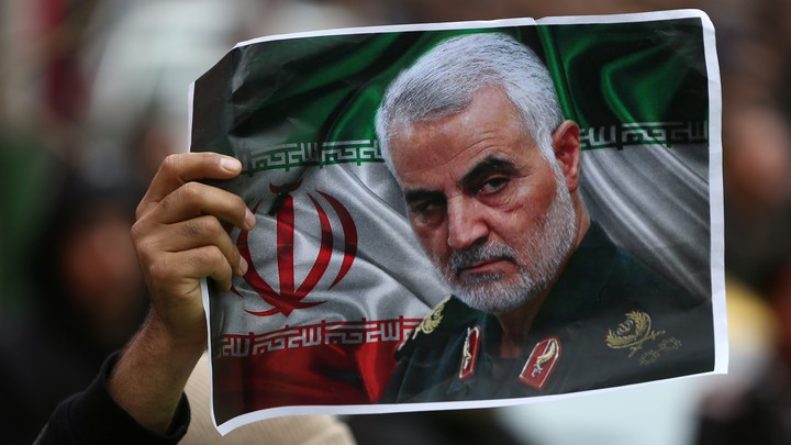 A protester holds up a picture of late General Qassem Soleimani.