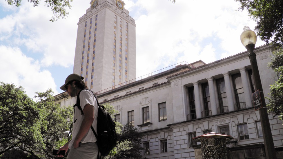 A student walks in front of a clock tower at UT Austin